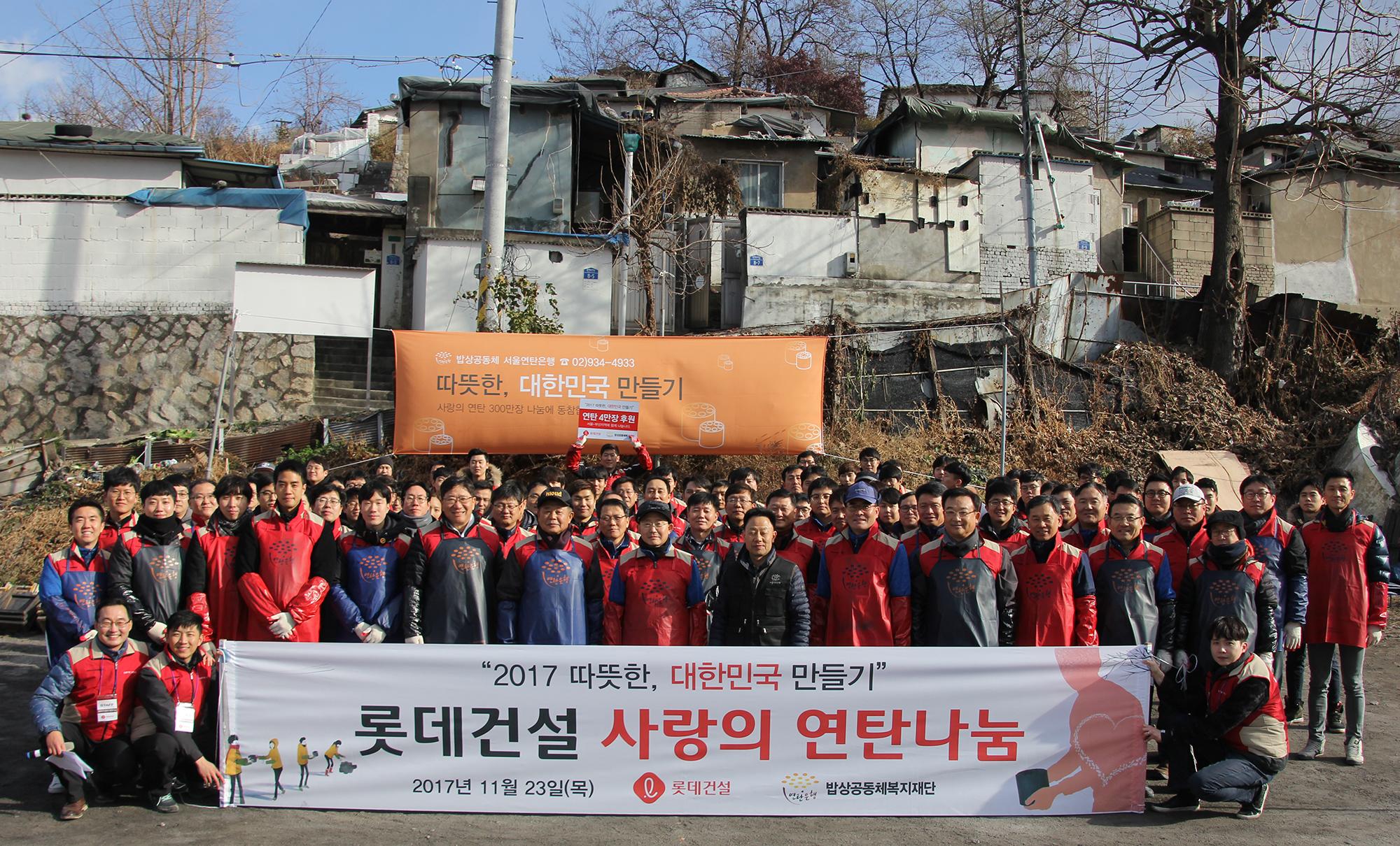 롯데건설 임직원들이 연탄나눔 봉사활동 단체촬영을 하고 있다.JPG