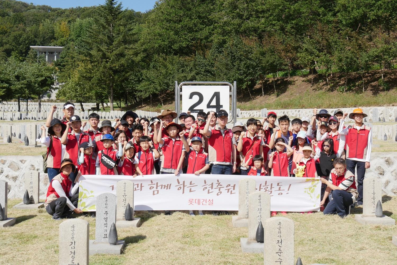 롯데건설 임직원 가족들이 자매결연 맺은 묘역 앞에서 봉사활동 기념 촬영을 하고 있다.JPG